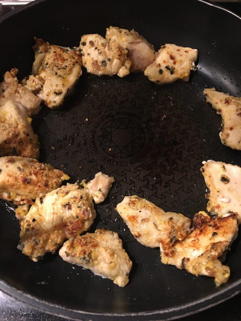 片栗粉をまぶした鶏肉をフライパンで焼く