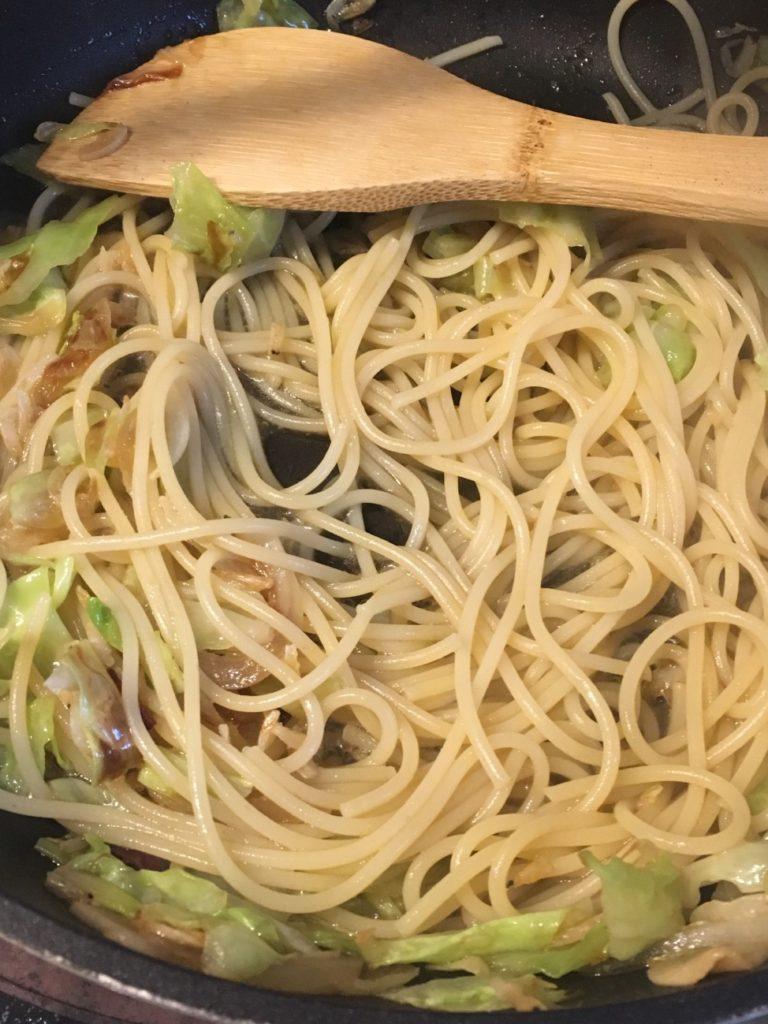 茹でたパスタを加え、醤油と塩こしょうで味をととのえる