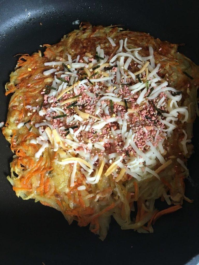 炒めたジャガイモのガレットにふりかけとピザ用チーズをふりかける