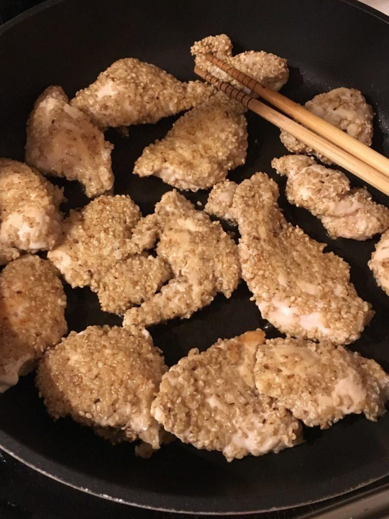 ごまをまぶした鶏肉をフライパンで炒める