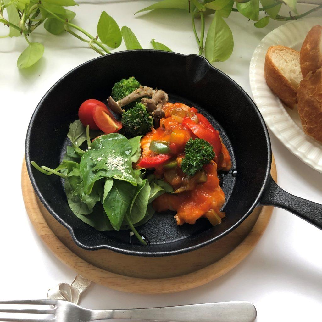 スキレットにサラダとキノコとブロッコリーの付け合せと一緒に盛り付けたラタトゥイユチキン
