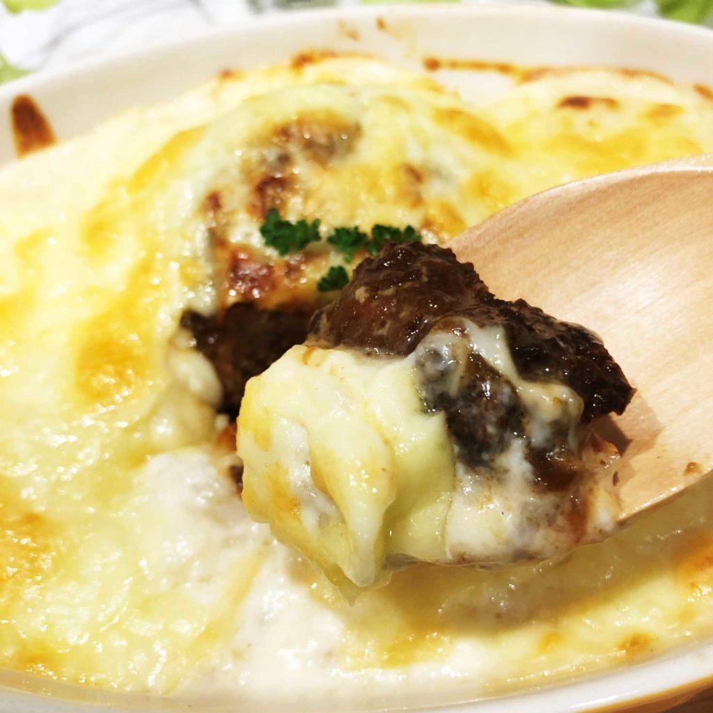 ホワイトソースとチーズと絡み合う煮込みハンバーグ