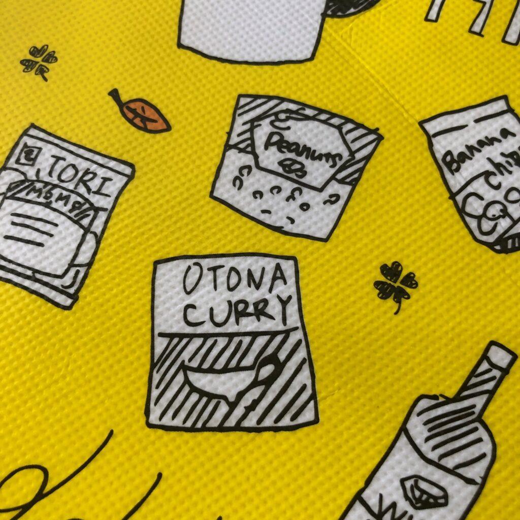 業務スーパーの黄色のエコバッグに描かれてる大人カレー・ピーナッツ・バナナチップスなど