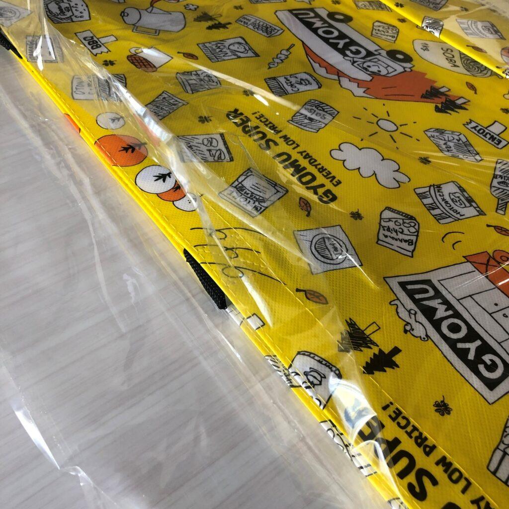 透明な袋で梱包されてる業務スーパーの黄色いエコバッグ