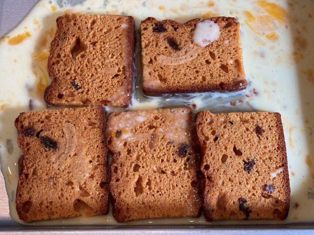 バットに並べたスパイスケーキに卵液をかけて染み込ませる