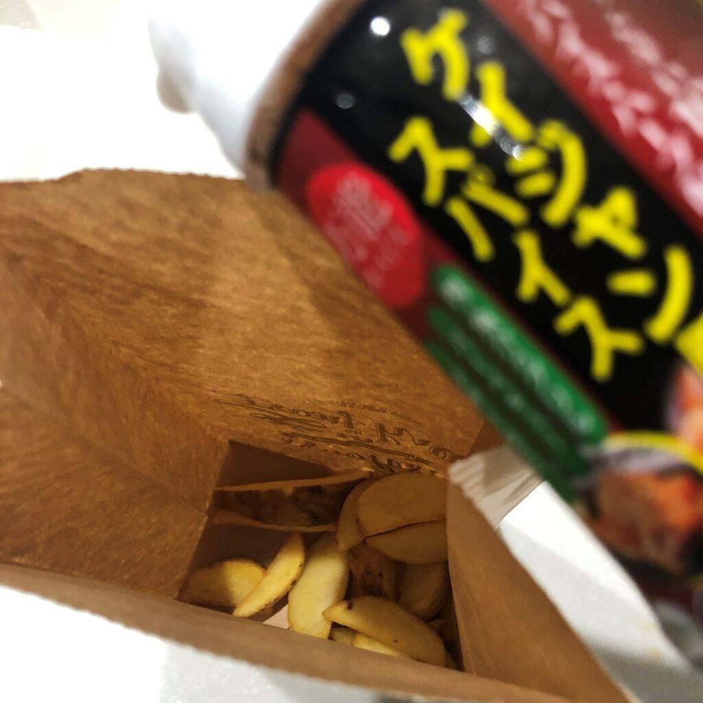 揚げたポテトを紙袋に入れて業務スーパーのケイジャン風スパイスを振りかける