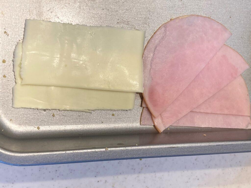 スライスハムとスライスチーズを半分に切る