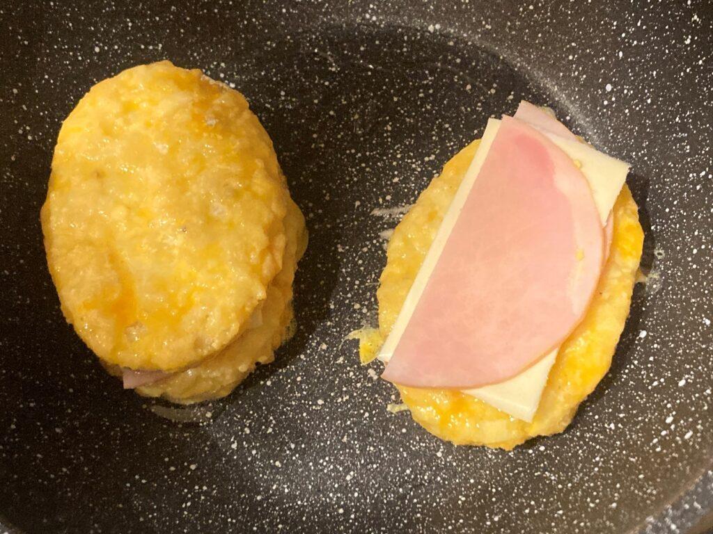 フライパンでハムチーズを挟んだ卵液につけたハッシュブラウンを焼く