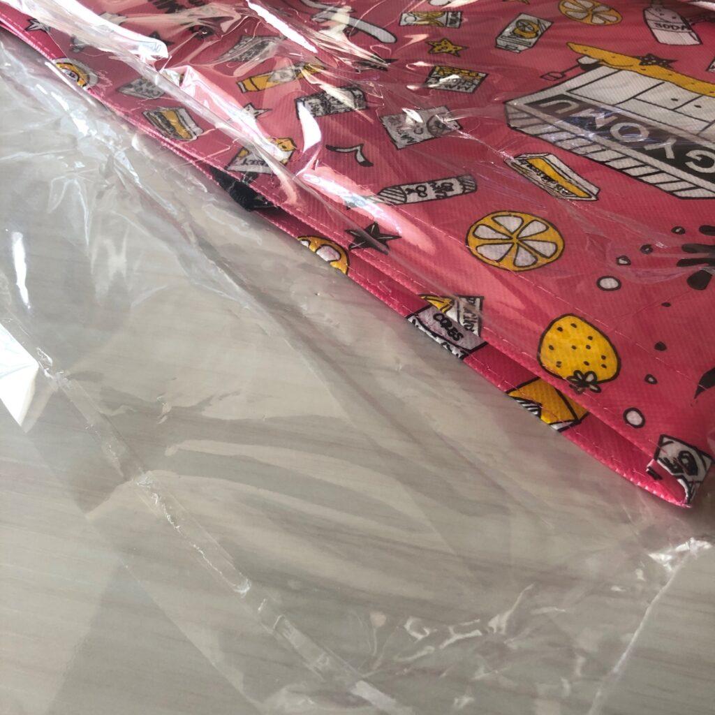 ビニールで包装されてる業務スーパーのピンク色のエコバッグ