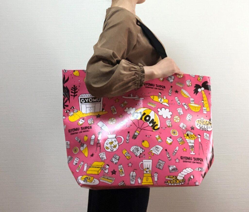 業務スーパーのピンク色のエコバッグを方から下げた女性