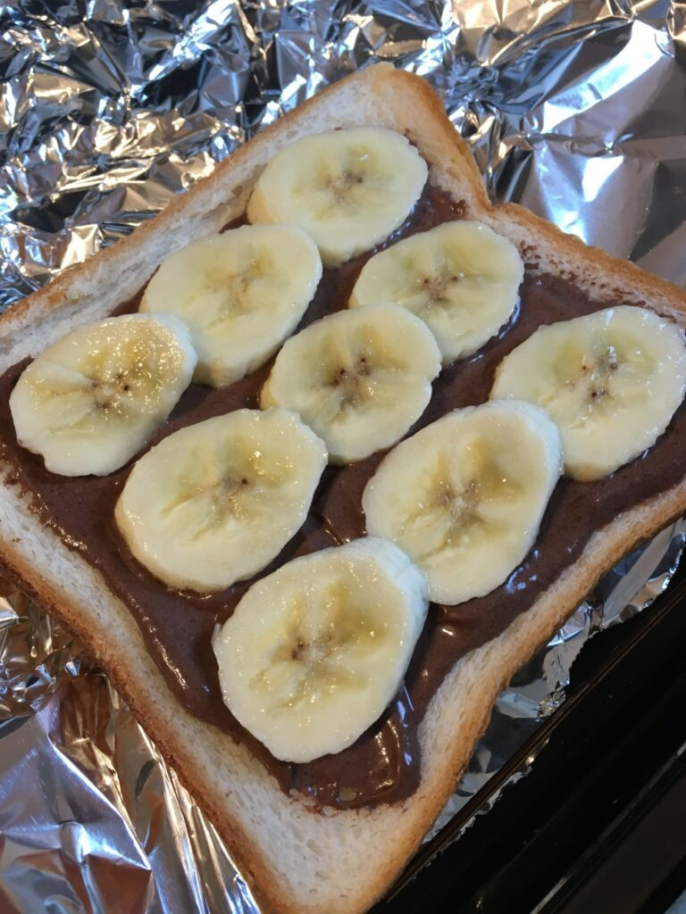 チョコレートトリュフを塗ったトーストの上に並べられたバナナ